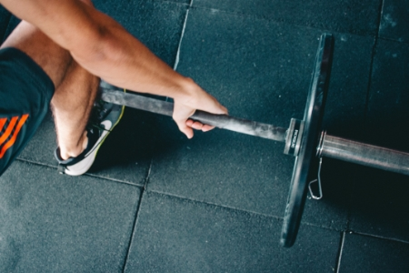 man squatting holding barbell with weight on